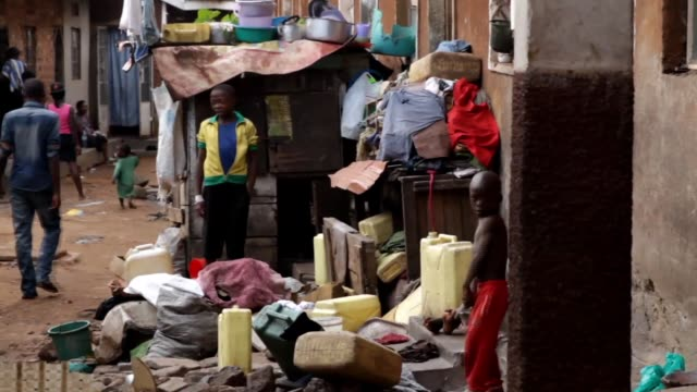 kids play in slum alley adults walking and talking shot of toilets and bathrooms sign - kampala stock videos & royalty-free footage