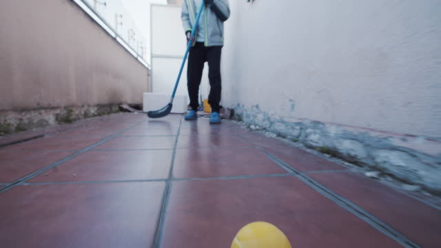 kids playing ad hoc hockey on balcony - moving image stock videos & royalty-free footage