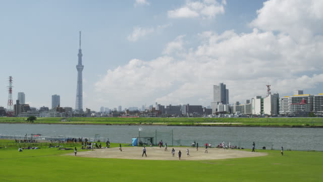 kids playing baseball along arakawa river in tokyo,japan - flussufer stock-videos und b-roll-filmmaterial