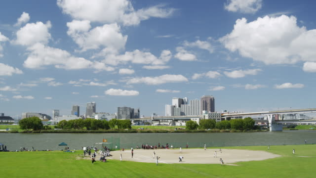 stockvideo's en b-roll-footage met kids playing baseball along arakawa river in tokyo,japan - waterkant