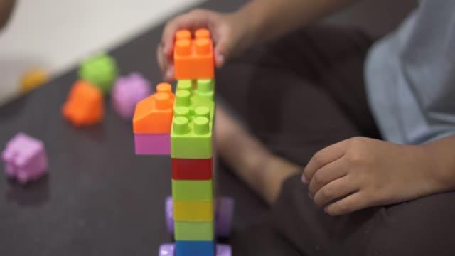 vidéos et rushes de gosses jouant des blocs en plastique colorés - jeu de construction