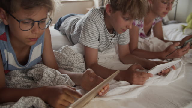 kids playing digital tablets in bedroom - dipendente video stock e b–roll