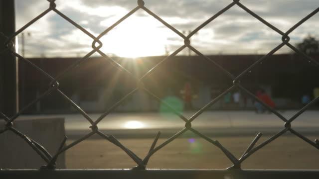 kinder spielen fußball im park - zaun stock-videos und b-roll-filmmaterial