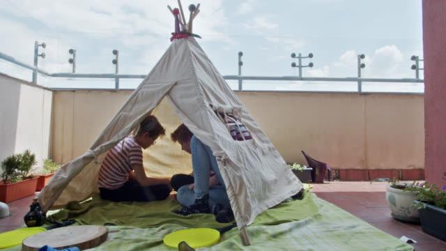 vídeos de stock, filmes e b-roll de crianças brincando em tenda de tenda de tenda na varanda - varanda