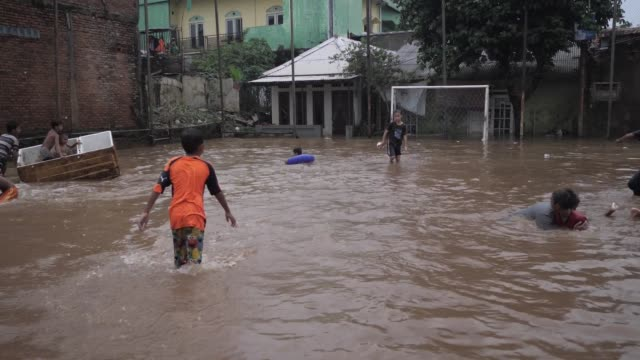 kids playing in the flooded water. heavy rains triggered widespread flood in jakarta inundating thousand homes. - jakarta stock videos & royalty-free footage