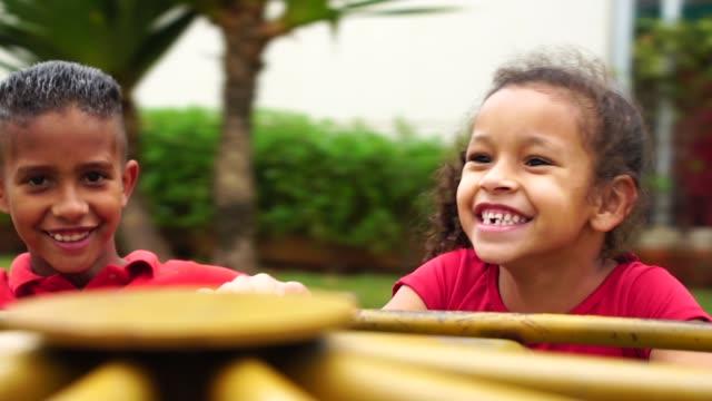 vídeos de stock, filmes e b-roll de crianças brincando em rotatória no parque - brincar