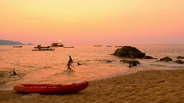 kids playing on sunset beach