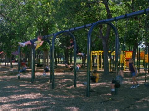 kids playing on swings. - 屋外遊具点の映像素材/bロール
