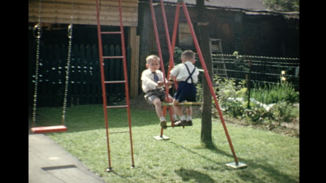 1953 home movie kids playing on swingset / toronto, canada - swing play equipment stock videos and b-roll footage
