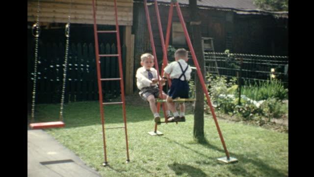 vídeos de stock e filmes b-roll de 1953 home movie kids playing on swingset / toronto, canada - equipamento de parque infantil