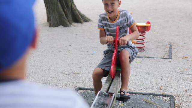 vídeos y material grabado en eventos de stock de niños jugando en teeter totter - balancín