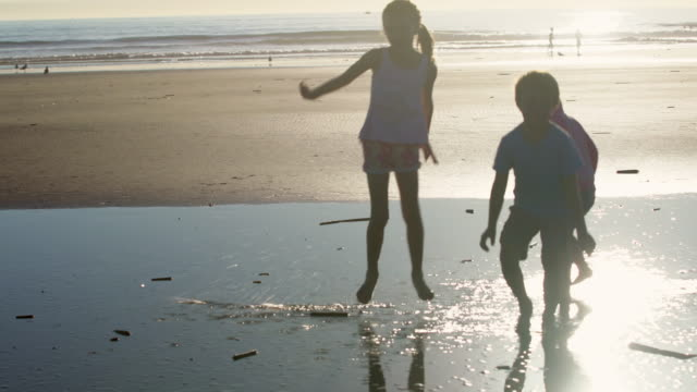 ws kids playing on the beach at sunset - brother stock videos & royalty-free footage