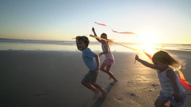 ws sm kids playing on the beach at sunset - 4 5 anni video stock e b–roll