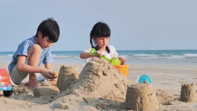 kids playing sandbox on the beach.happy family enjoy summer vacation on the beach.couples relationship.vacations - istock - sibling stock videos & royalty-free footage