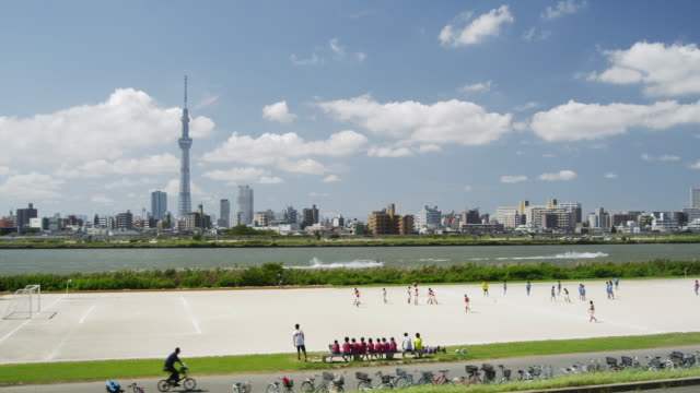 kids playing soccer along arakawa river in tokyo,japan - riverbank stock videos & royalty-free footage