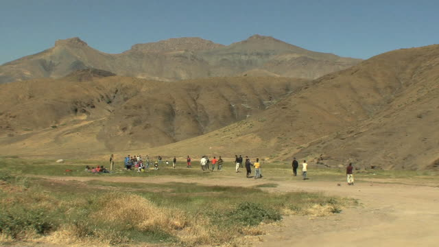 ws kids playing soccer at foot of atlas mountains, morocco - mountain range stock videos & royalty-free footage