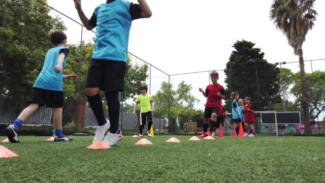 kids playing soccer - boys and girls on a football court in training - recreational pursuit stock videos & royalty-free footage