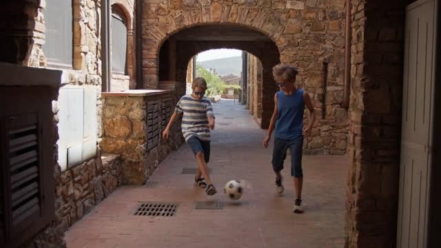 bambini che giocano a calcio in una piccola città - town video stock e b–roll