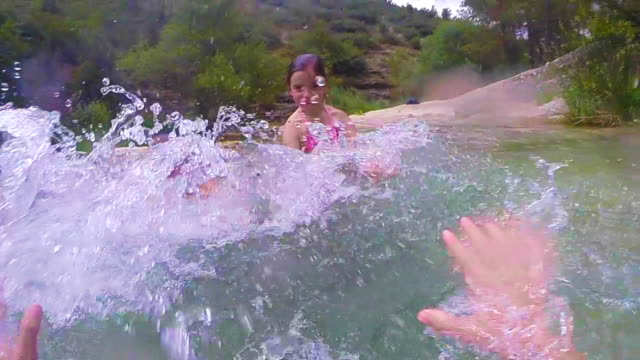 Kids playing splashing each other while taking a bath on summer in the river with slow motion and personal point of view.
