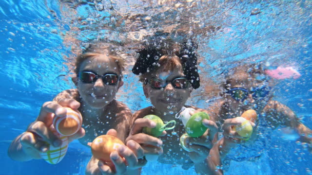 kids playing underwater during summer easter - girl swimming costume stock videos & royalty-free footage