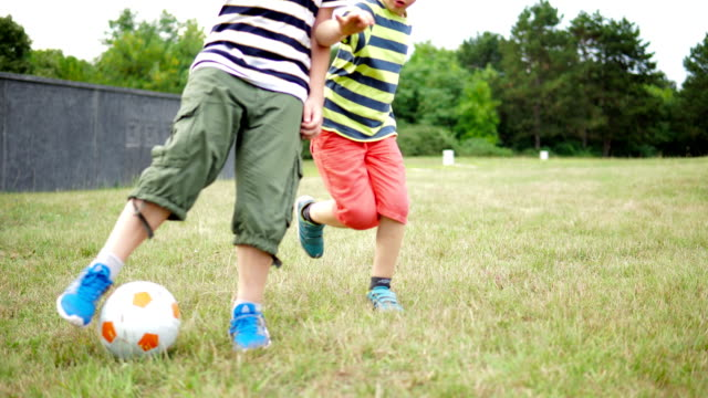 kids playing with a football in a field - kicking stock videos & royalty-free footage
