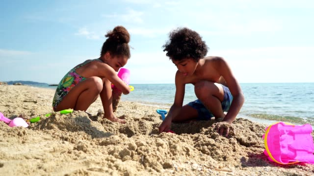 kids playing with sand on the beach - innocence stock videos & royalty-free footage