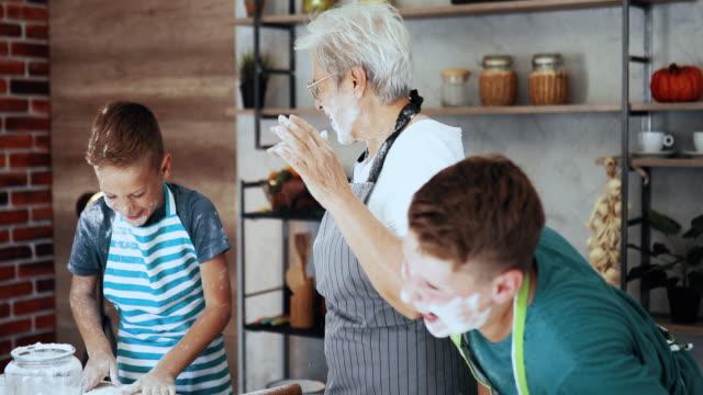 vidéos et rushes de gosses jouant avec leur grand-mère dans la cuisine, faisant un gâteau - grand mère