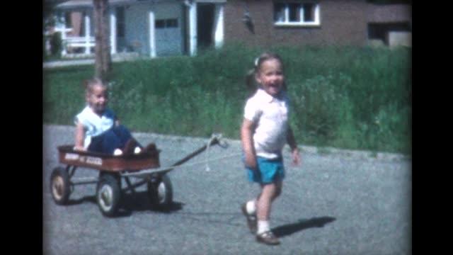 1960 kids pulling friend in Radio Flyer wagon