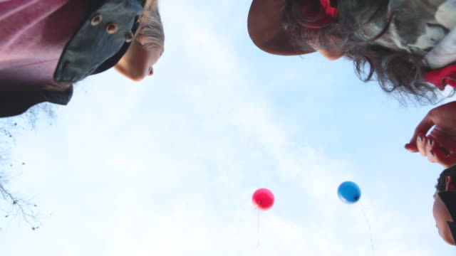 ms kids releasing balloons in air / los angeles, california, united states  - loslassen aktivitäten und sport stock-videos und b-roll-filmmaterial