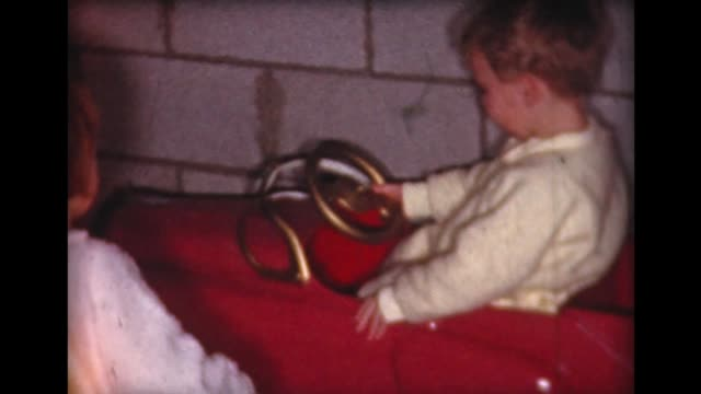 vídeos de stock, filmes e b-roll de 1961 kids ride in new, red, christmas fire truck - home movie