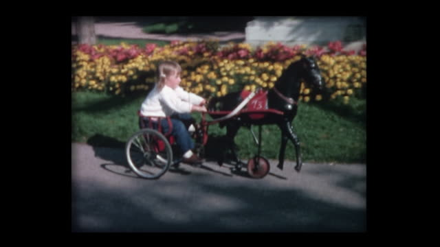 1964 kids ride pedal horses and pedal carts - home movie stock-videos und b-roll-filmmaterial