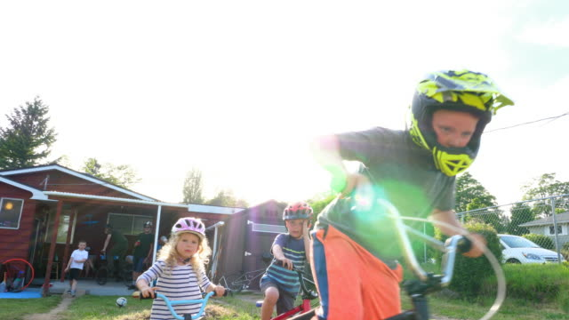 ms kids riding bmx bikes in backyard on summer evening - bmx cycling stock videos and b-roll footage