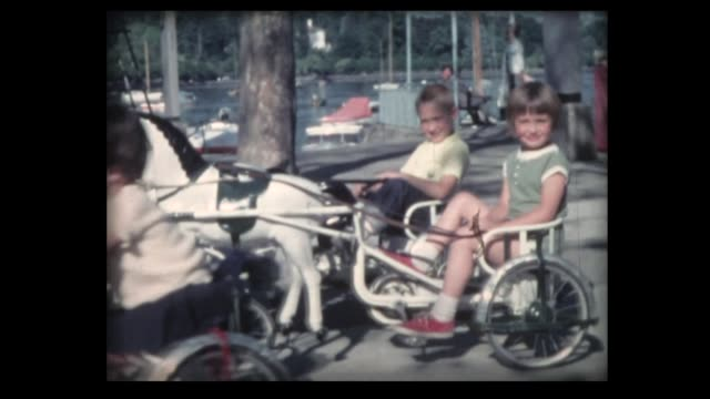 1962 kids riding pedal horses in swiss park - tricycle stock videos & royalty-free footage