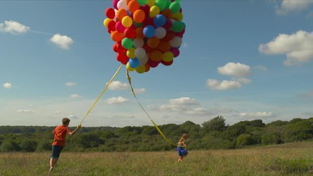 vídeos de stock, filmes e b-roll de ms kids running around field holding onto large bunch of balloons - bexiga