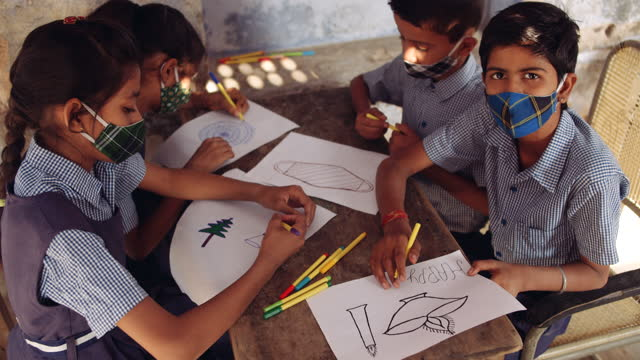 kids seated on a table drawing and sketching on white paper with felt pens and enjoying themselves and being artistic and creative- boy drawing a diya for diwali and a girl is drawing a christmas tree for christmas - elementary school stock videos & royalty-free footage