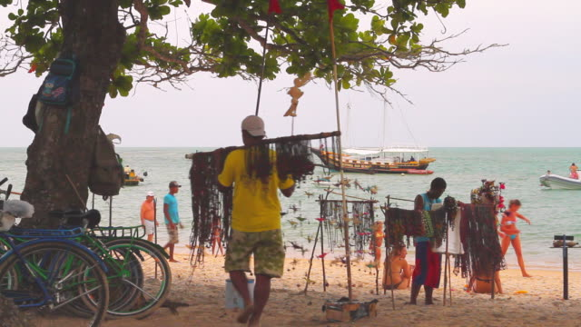 ws kids selling trinkets on beach with boat in background / trancoso, bahia, brazil - craft product stock videos & royalty-free footage