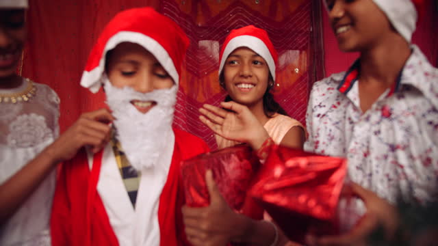 kids singing dancing making merry as they celebrate christmas with gits joy and laughter, slow-motion handheld - weihnachtsmütze stock-videos und b-roll-filmmaterial