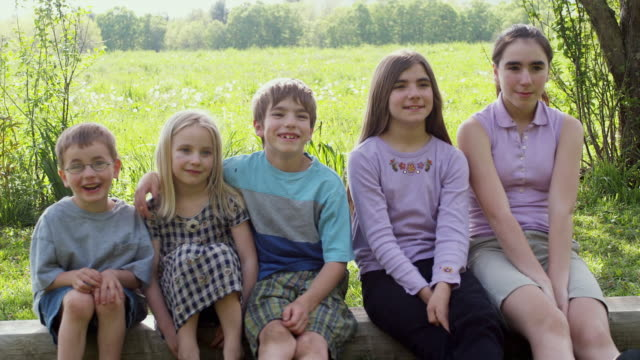 ms kids (4-13) sitting in a row, smiling / sunderland, vermont, usa - legs crossed at ankle stock videos and b-roll footage