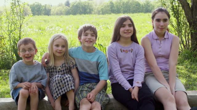 ms kids (4-13) sitting in a row, smiling / sunderland, vermont, usa - 4歳から5歳点の映像素材/bロール
