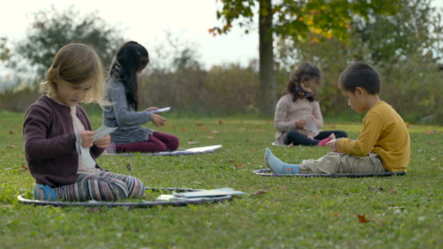 kids sitting in hula hoops on the ground in a modified outdoor classroom - preschool stock videos & royalty-free footage