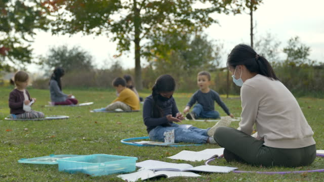 kids sitting in hula hoops on the ground in a modified outdoor classroom - fatcamera stock videos & royalty-free footage
