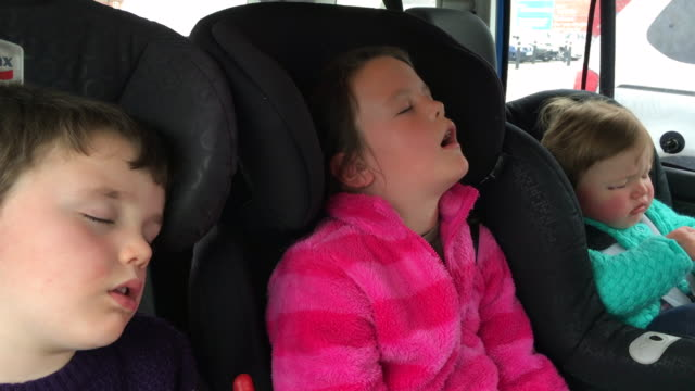 Kids sleeping in the back of a car after a long journey
