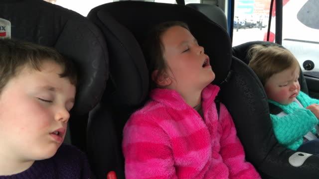 Enfants dormant à l'arrière d'une voiture après un long voyage