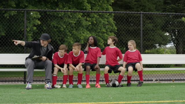 Kids soccer team celebrating with coach on the bench