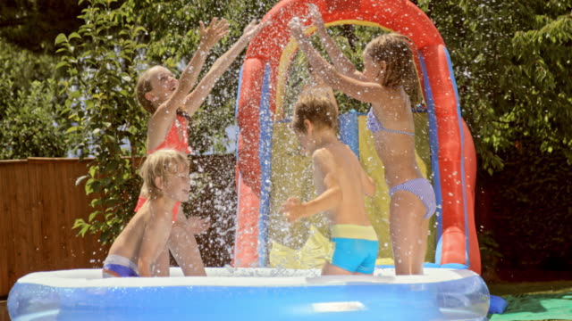 slo mo kids splashing water in inflatable pool and laughing - water slide stock videos & royalty-free footage