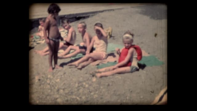 1962 kids sunning on lake beach, switzerland - towel stock videos and b-roll footage