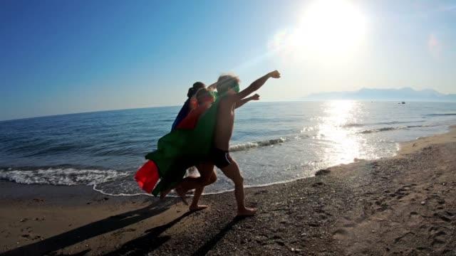 vídeos de stock, filmes e b-roll de super-heróis dos miúdos que jogam na praia - super herói