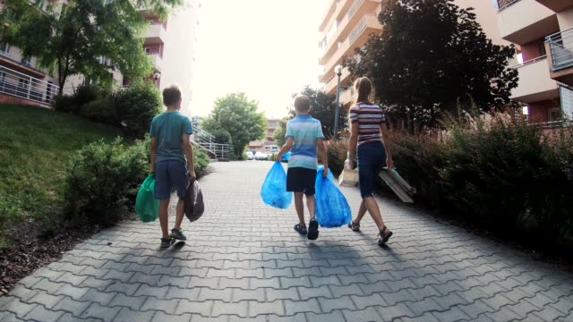 vídeos de stock e filmes b-roll de kids taking out the segregated garbage - lixo