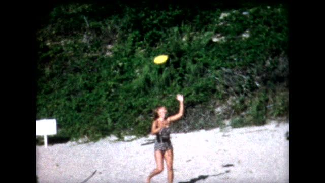 1958 kids tumble and play frisbee on beach - schwimmweste stock-videos und b-roll-filmmaterial