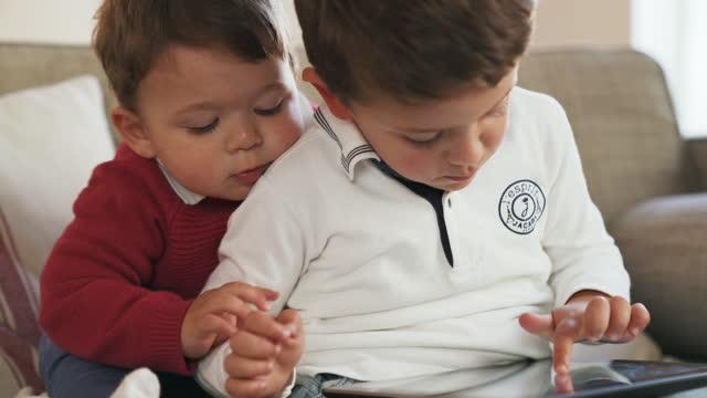 vídeos de stock, filmes e b-roll de crianças usando um tablet digital - vista frontal